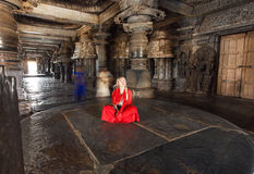 Beautiful woman in traditional indian dress sitting on stone floor of 12th century temple Hoysaleswara, India. Stock Photos