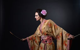 Beautiful woman in traditional Japanese kimono with katana Stock Photo