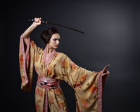Beautiful woman in traditional Japanese kimono with katana Royalty Free Stock Image