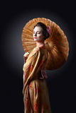 Beautiful woman in traditional Japanese kimono with umbrella Stock Photography