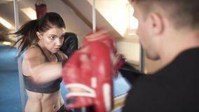 Beautiful woman training boxing in the gym. View from the trainers back. stock video footage