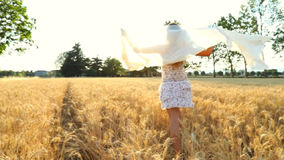 A beautiful woman with a transparent veil in wheat field. Young girl having fun at sunset light in the middle of nature and trees with the wind in the hair / stock video footage