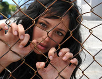 Beautiful woman trapped behind a fence. Beautiful brunette woman grasping onto the links of a chain fence trapped in the city Stock Image