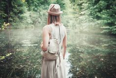 Beautiful woman traveler with backpack near river in forest Stock Photos