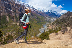 Beautiful Woman Traveler Backpacker Mountains Path.Young Girl Looks Right Way and Take Rest.North Summer Snow Landscape Royalty Free Stock Photo