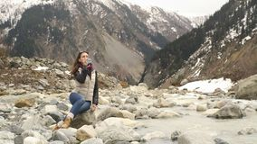 Beautiful woman traveler drinks water near a mountain river on a background of mountains stock video footage