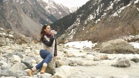Beautiful woman traveler drinks water near a mountain river on a background of mountains. Beautiful woman resting on a rock in the river and drinking water stock video