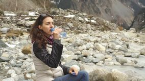Beautiful woman traveler drinks water near a mountain river on a background of mountains. Beautiful woman resting on a rock in the river and drinking water stock footage