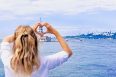 Beautiful woman makes heart shape with hands on view of Maidens Tower,a popular destination in Istanbul,Turkey. Beautiful woman traveler makes heart shape with stock photos