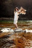 Beautiful woman traveler standing on rocks in river and playing Royalty Free Stock Images