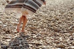 Beautiful woman traveler walking barefoot  at river beach, legs Royalty Free Stock Image