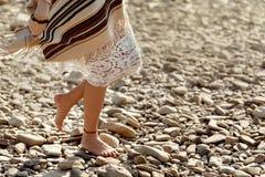 Beautiful woman traveler walking barefoot  at river beach, legs Royalty Free Stock Photo