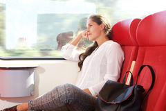 Beautiful woman traveling by train looking out the window Royalty Free Stock Photos