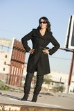 Beautiful Woman in a Trenchcoat. Beautiful woman in black trenchcoat and sunglasses at train yard Royalty Free Stock Image