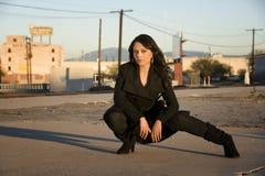 Beautiful Woman in a Trenchcoat. Beautiful woman wearing black trenchcoat in urban setting Royalty Free Stock Image