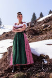 Beautiful woman trendy in the Dirndl. Beautiful woman in the Dirndl Dress stands with arms folded in the middle of the Alps between tree stumps and snow fields stock photography