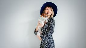 Beautiful woman in trendy dress and hat with dog stock image