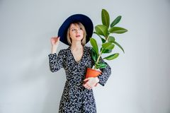 Beautiful woman in trendy dress with plant in a pot. Stay near white wall at home stock images
