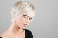 Woman with trendy blond hair. Portrait of beautiful young woman with trendy blond hairstyle, studio background Stock Images