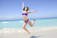 A beautiful woman on a tropical beach cuba. Jumping Stock Photo
