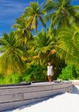 Beautiful woman on tropical beach. Walking along boardwalk on luxury exotic resort, enjoying summer vacation on Maldives Stock Photography