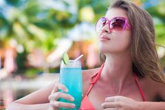 Beautiful woman with tropical cocktail in the pool. Remote tropical beaches and countries. travel concept Royalty Free Stock Image