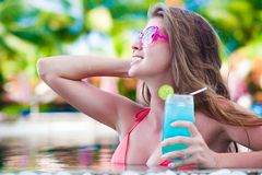 Beautiful woman with tropical cocktail in the pool. Remote tropical beaches and countries. travel concept Stock Photo
