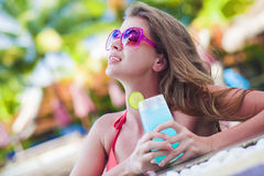 Beautiful woman with tropical cocktail in the pool. Remote tropical beaches and countries. travel concept Stock Image
