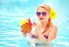 Beautiful woman with tropical fruit cocktail in pool Royalty Free Stock Photos