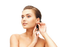 Beautiful woman trying on gold earrings Stock Images