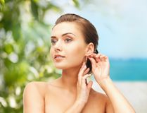 Beautiful woman trying on gold earrings Royalty Free Stock Photography