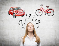 A beautiful woman is trying to chose the most suitable way for travelling or commuting. Two sketches of a car and a bicycle are dr Royalty Free Stock Photos