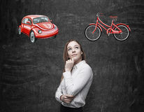 A beautiful woman is trying to chose the most suitable way for travelling or commuting. Two sketches of a car and a bicycle are dr Royalty Free Stock Photography