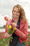 Beautiful woman with tulips in the fields Royalty Free Stock Image