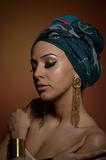 Beautiful woman with turban. Young attractive female with turban and golden accessories. Beauty fashionable woman Stock Photography