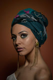 Beautiful woman with turban. Young attractive female with turban and golden accessories. Beauty fashionable woman Royalty Free Stock Photo