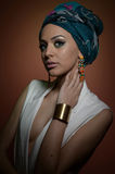Beautiful woman with turban. Young attractive female with turban and golden accessories. Beauty fashionable woman Stock Photos