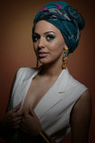 Beautiful woman with turban. Young attractive female with turban and golden accessories. Beauty fashionable woman Royalty Free Stock Images
