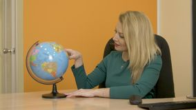 Beautiful woman turning globe map and looking on countries and continents. For tourist trip in business office. Business woman looking on world globe in travel stock video footage