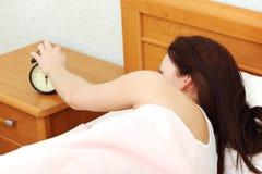 Beautiful woman turning off an alarm clock. Royalty Free Stock Photos