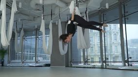 Beautiful woman turns over in the air holding on yoga hammock in studio. Many white empty hammocks around. Modern. Cityscape behind window stock video
