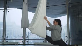 Beautiful woman turns over in the air holding on yoga hammock in studio. Many white empty hammocks around. Modern. Cityscape behind window stock footage