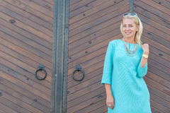 Beautiful woman in turquoise dress in street Royalty Free Stock Image