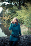 Beautiful woman with turtleneck on the phone in the city Royalty Free Stock Photo