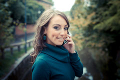 Beautiful woman with turtleneck on the phone in the city Royalty Free Stock Images