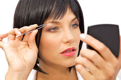 Beautiful Woman Tweezing her eyebrows Royalty Free Stock Images