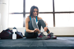 Beautiful woman tying shoelaces. At gym royalty free stock photo