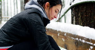 Beautiful woman tying shoelaces during snowfall. Close-up of beautiful woman tying shoelaces during snowfall stock footage