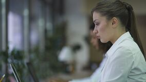 Beautiful woman typing on laptop, working on business project with focused face. Stock footage stock video