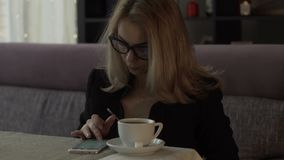 Beautiful woman typing message on screen mobile phone on background coffee cup. At table in cafe. Woman chatting in smartphone during coffee break stock video